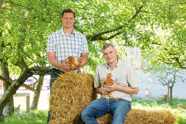 Josef Ruloff Sitzt Auf Einem Strohballen Während Markus Casagrande Danebensteht, Beide Halten Ein Ländle Wiesenhuhn In Der Hand