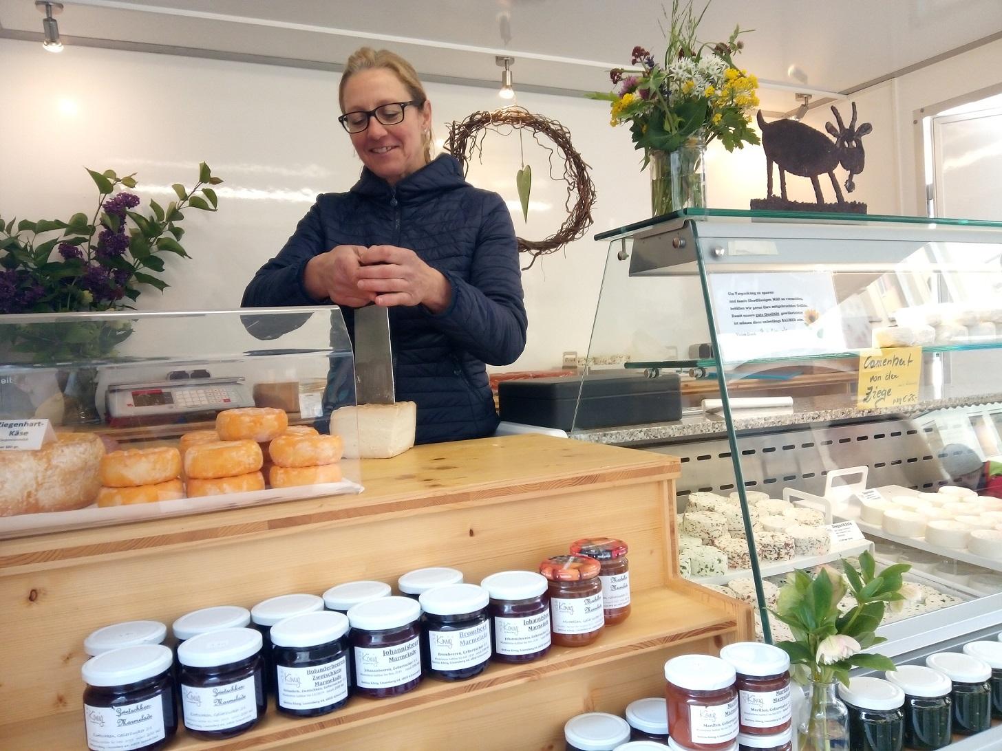 Bettina König Steht Im Hofladen Und Schneidet Käse, Auf Dem Foto Sind Verschiedene Produkte Des Hofladens Zu Sehen
