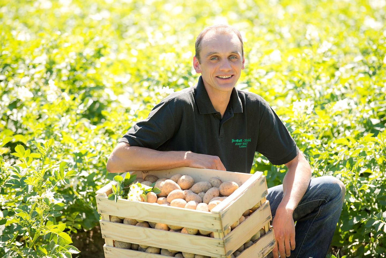Thomas Bischof Kniet In Einem Kartoffelfeld, Dabei Lehnt Er Sich An Einer Kiste An, Die Mit Kartoffeln Gefüllt Ist Und Lächelt In Die Kamera