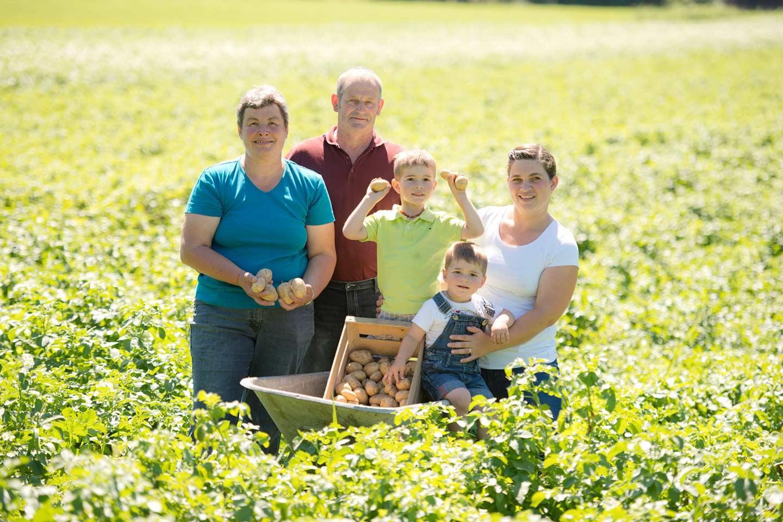 Familie Burtscher Steht Inmitten Von Einem Kartoffelacker Mit Einer Kiste, Welche Mit Ländle Kartoffeln Gefüllt Ist