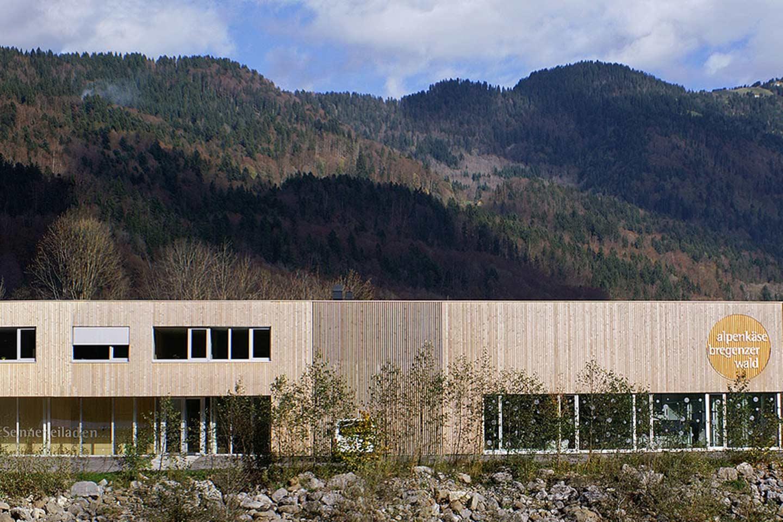 Auf Dem Bild Ist Das Gebäude Der Alpenkäse Bregenzerwald Sennerei Zu Sehen, Außerdem Sieht Man Im Hintergrund Ein Bergpanorama