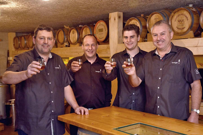 Die Männer Von Der Familie Broger Stehen Nebeneinander Mit Einem Glas Whisky In Der Hand, Dabei Lächeln Sie In Die Kamera