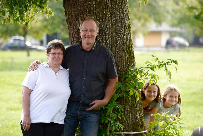 Albert Büchele Steht Mit Seiner Frau Im Arm Vor Einem Baum, Während Zwei Kinder Hinter Dem Baum Hervorschauen